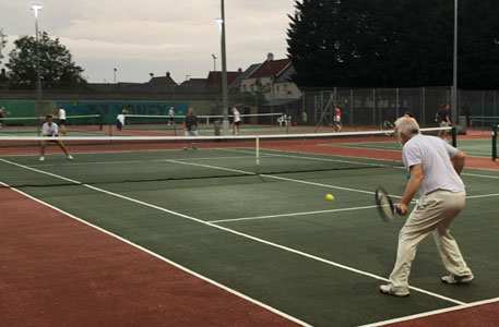 adult tennis at a group coaching session