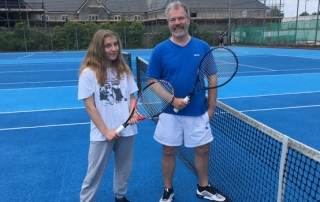 Chairman Dan and Kitty Standing on a blue court holding rackets