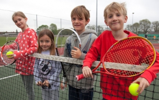 four juniors with rackets on a net