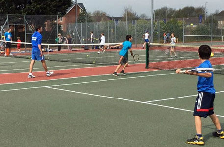 Juniors Playing tennis on a tennis court in a coaching session