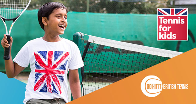 Child smiling with a raccket in a tennis for kids shirt