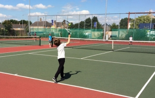 Mini tennis player serving on a green court