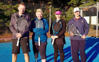 Wells A team Dave, Julia, Marie and Dave C posing for a team picture on a blue tennis court in the sunshine