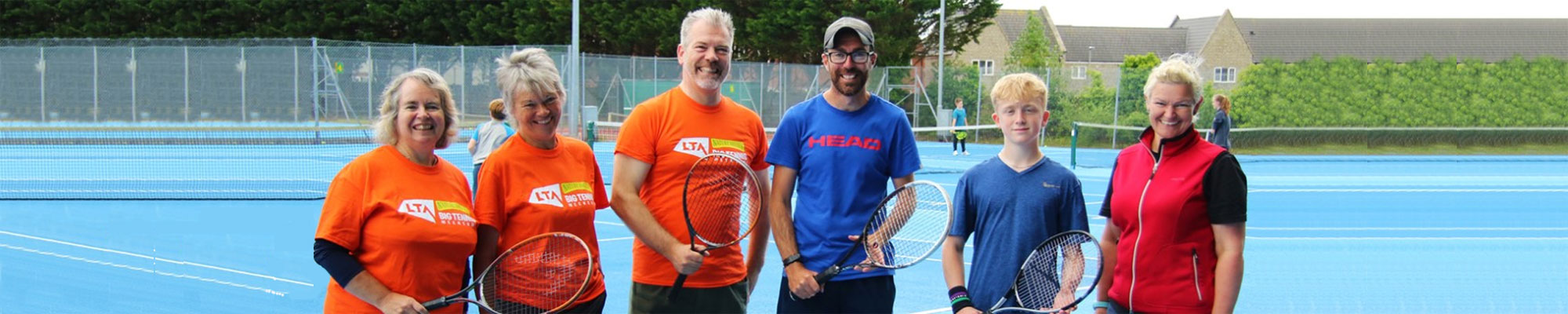 Members of Wells Tennis Club standing on a blue court