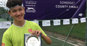 A young player holding the plate for winning the road to wimbledon county event