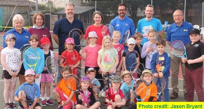 Children with their rackets standing and sitting infront of members of Wells Tennis Clubs committee
