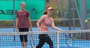 two female tennis players hitting balls on a blue court