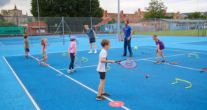 mini tennis kids practicing on a blue court with the coach