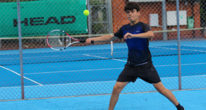 junior playing a forehand on a blue court